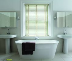 Rustic off white wooden venetian blinds in a contemporary white bathroom.