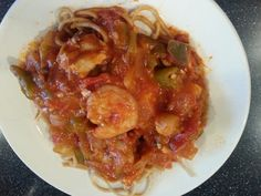 Seafood Italiano   1 tablespoon olive oil 1 large onion, chopped 1 green pepper, chopped 1/2 pound okra, 12 inch slices 2 garlic cloves, finely chopped 1/2 cup white wine Juice from 1 lemon 3 cups good quality tomato sauce 1/4 teaspoon red pepper flakes 1 lb large shrimp, peeled and deveined 1/2 pound bay scallops, rinsed 1 tilapia filet, cut into bite sized squares 1/2 cup basil leaves 1/4 cup chopped parsley 12 ounces Angel hair pasta (Vermicelli), cooked and drained