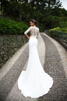 Marvelous mermaid silhouette wedding gown Merill consists of a classy lace bodice with bateau neckline and beautiful cotton skirt. The lace corset is manually embellished with beads and Swarovski gems. The back is tightly buttoned up and zipped.