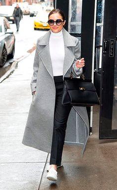 Olivia Culpo usa turtleneck branca, calça de alfaiataria preta, casaco sobretudo cinza, tênis branco e bolsa estruturada preta, finalizando com óculos redondo