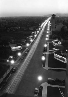 "(1928)*# - Aerial view of a well lit Wilshire Boulevard at night. The ORIGINAL BROWN DERBY restaurant is visible on the right. Note the numerous signboards on both sides of Wilshire Blvd. The ""Wilshire Special"" streetlights do a good job lighting up the Boulevard."