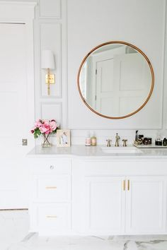 whitewash bathroom elevated by intricate moldings, a marbled floor, and polished brass accents.
