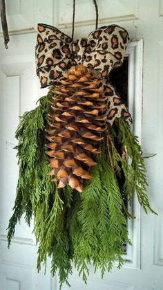 fresh greenery with burlap ribbon and giant pinecone easy christmas door decor