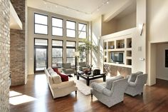 Here's another sprawling open-plan living room, this time bracketed by full height windows and a rustic brick wall. The white walls and built-in shelving match a lengthy traditional sofa at center, paired with textural armchairs and a dark wood coffee table.