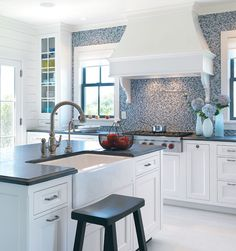 Mosaic tiles create a majestic back wall in the country kitchen, which features a French Provincial range hood.