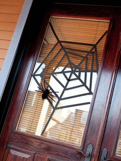 Webbed Window Covering  Turn a front door window into a spider's clever trap with black crafts tape. Start with three long strips of tape, creating an off-center X shape with two pieces and using the third to cut across the middle of the X, dividing your glass window into six sections. Starting at the center, add tape strips to each section until a web starts to take shape.