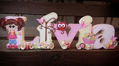 Nome  Lívia em MDF decorado com a  técnica de scrapdecor, letras  foradas com  papéis de scrapboook, flores feitas  a partir de  furadores. Menina  com  flores comprada  no site da silhuette Design.