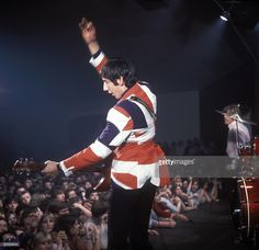 Photo of Pete TOWNSHEND and The Who; Pete Townshend performing live onstage, wearing union jack jacket, doing 'windmill' arm, showing audience watching