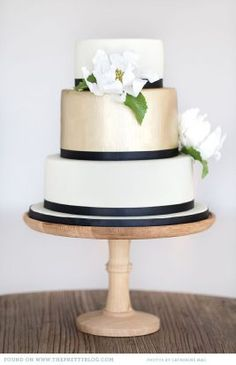 Navy and gold wedding cake- substitute coral flowers {via theprettyblog.com}