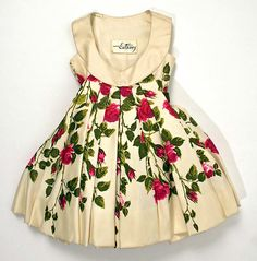 Little girl's floral-print silk dress with green velvet ribbon sash (back), by Mr. Luis Estévez, American, 1958. Worn with silk cape with matching floral-print silk lining.