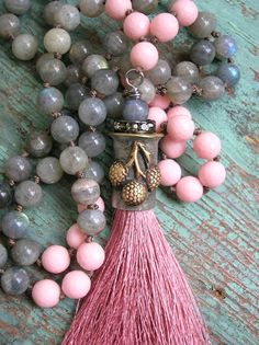 A long, hand-knotted necklace featuring one of my signature hand-forged tassel caps! Embellished with a cluster of berries, capped with rhinestones and with a lush rosy pink tassel snugged inside, it swings from a strand of glowing labradorite gemstones. Accented with faceted pink stones for a fun pop of color... Layer it with your favorite chains or wear it alone. Such a breeze to wear...just slip it over your head and go! Perfect with maxi-dresses or shorts and a tee... Please note al...