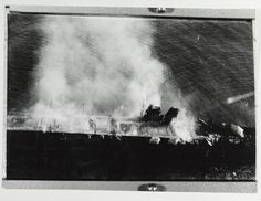 Midway,  Japanese aircraft carrier Hiryu burning, shortly after sunrise on 5 June 1942, a few hours before she sank. Photographed by a plane from the carrier Hosho. Note collapsed flight deck at right. Part of the forward elevator is standing upright just in front of the island, where it had been thrown by an explosion in the hangar