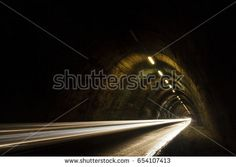 Old tunnel at night with white blurred car lights