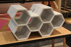Bees and Honey by Christopher Roy combines wood and marble in a unique way. The marble shelving unit on top is in a honeycomb shape