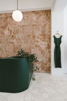 Pink Travertine and Rusty Velvet in a Coolly Minimalist Cape Town Boutique | new store | south africa store | retail store | newest retail stores | interior design | sleek interior design stores | contemporary stores | modern armchair | orange armchair
