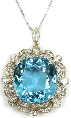 Early 20th century single stone aquamarine and diamond cluster pendant/brooch, c.1920, the cushion shaped aquamarine claw set to a scalloped edge double diamond border, spaced by eight collet set pear shaped diamond accents, mounted in platinum and gold, the brooch fitting and suspension loop both detachable. Via S.J. Philips.