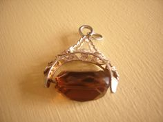 A well detailed silver charm of an amber coloured glass stone . The amber stone spins in the mount which is very well made.Lots of cut out
