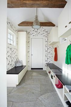 Whimsical bird-print wallpaper transforms a mudroom by TR Building & Remodeling Inc. into an enchanting space worthy of a pause when you're doffing a dripping raincoat.