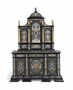 AN ITALIAN ORMOLU-MOUNTED IVORY AND HARDSTONE-INLAID EBONY AND EBONISED CABINET PROBABLY FLORENCE, SECOND HALF 19TH CENTURY Decorated overall with Berainesque motifs including rinceaux, putti and mythical birds, and inlaid with various semi-precious stones including lapus lazuli, malachite and various agates and marbles, the superstructure with domed pediment surmounted by a later sodalite finial, above three walnut-lined cupboard doors each enclosing a single shelf, flanked by giallo di…