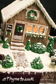Gingerbread house with snow covered bushes, trees, and a stone path that leads up to the front door.
