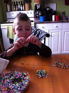 Ethan makes necklaces, each with a blue bead, to raise juvenile arthritis awareness!