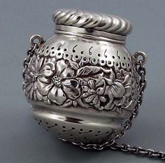 """Gorham Repousse Sterling Silver Tea Ball    A large antique sterling silver tea ball by Gorham circa 1890 with fine piercing and a wide chased band of decoration around the center. 1 7/8"""" long.    Price: $795.00"""