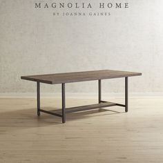 With a play of vertical and horizontal lines, this dining table makes the perfect gathering spot for friends and family. Featuring a distressed poplar plank top and an industrial-vintage appearance, it's part of the Magnolia Home Collection by Joanna Gaines.