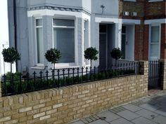 Yellow brick garden wall metal rail and gate bay and buxus topiary Clapham Battersea Balham London (2)