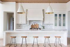 A pair of white and gold cone pendants, Goodman Hanging Lamps, illuminates an extra-long kitchen island topped with white quartz fitted with a farmhouse sink and deck mount faucet lined with wood and iron counter stools, Wisteria Smart & Sleek Stools.