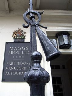 """Maggs Bros Ltd rare bookshop, located on one of London's poshest squares in Mayfair, boasts a Royal warrant just inside the front door. Inside No 50 Berkeley Square ... earnest young men in expensive suits sit at desks covered in large old brown books, which they flog to largely millionaire collectors that occasionally step through the front door."""" Note the link snuffer, which was used to extinguish torches carried by link boys."""