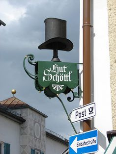 hat shop in Bad Tolz, Germany Blade Sign, Metal Signage, Storefront Signs, Pub Signs, Shop Fronts, Signage Design, Advertising Signs, Store Signs, Hanging Signs