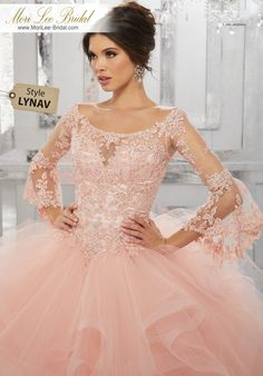 Style LYNAVBeaded Lace Appliqués on a Flounced Tulle Ball GownThis Unique Quinceañera Ballgown Perfectly Combines Tradition with a Touch of Trend. Boho Bell Sleeves Pair Perfectly with a Full Ruffled Tulle Skirt. Colors Available: Champagne, Scarlet, Blush, White.