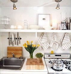 Storage idea for dishtowels—hanging them on hooks under cabinets