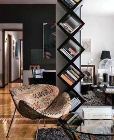 O apartamento dos publicitários Ângela e Marcone ganhou nichos pretos, em forma de losango para acomodar os livros, e paredes pretas para destacar as obras de arte garimpadas em viagens. O projeto é da arquiteta Andrea Buratto.