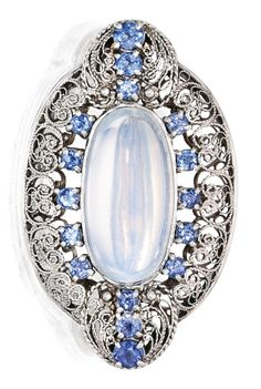 Ca. 1914-1933 Tiffany platinum, moonstone and sapphire brooch, Tiffany & Co., Designed by Louis Comfort Tiffany. Centring an oval-shaped cabochon moonstone measuring approximately 20.1 by 9.2 by 8.2 mm, within openwork surrounds set with 16 round sapphires, signed Tiffany & Co.