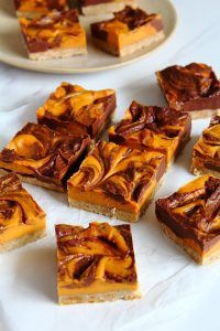 In one word…EPIC!!! These bars are incredible. A soft swirled fudge like chocolate and orange layer on top of a no bake coconut and pecan biscuit base. #recipe #pumpkin #orange #chocolate #biscuit #halloween @peachyshel