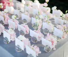 Tiny bud vases overflowing with hydrangeas serve as holders for guests' place cards.