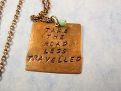 Beautiful hand stamped quote  Two roads diverged in a wood, and I—   I took the one less traveled by,   And that has made all the difference.