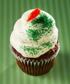 Gigi's Cupcakes - Carrot Cake: Carrot cake topped with a cream cheese frosting, decorative orange icing and green sugar crystals.