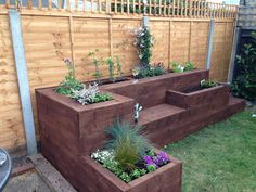 Raised flower bed I would make this out of sleepers but I like the different heights of the planting spaces.