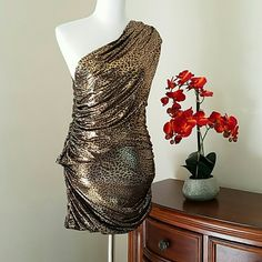Bebe Metallic Leopard Mini Dress Bebe Dress Metallic Leopard Mini Dress  A single toga strap wraps around the neck. Shiny and smooth metallic fabric is pixelated leopard print.  Pullover style Sleeveless Polyester/spandex/ nylon  Hand wash cold  Made in USA bebe Dresses Mini