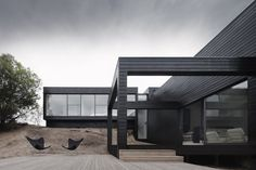 Burrowed into a sandy ridge on the Mornington Peninsula is a house by studiofour. Dark boxes spill down the slope while double height windows invite the outside in. Decks reach out to the native landscape which shelters the house from harsh winds. Public and private, positive and negative space, dark and light. Manmade and the natural. A holistic approach by the design studio ensures a bespoke home that addresses the site and the owner's needs.