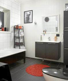 Badet er stramt innredet med kontrastfargene svart og hvitt. Rødt har her blitt brukt som aksentfarge for å piffe opp rommet. Innredningen er fra Coop Obs bygg, og badekaret er fra Sveberg.