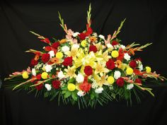 Large overhead casket spray with a summer mix of flowers designed by Loeffler's Flowers.