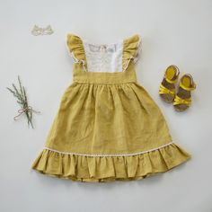 """Our dreamy Flutter Dress in Buttercup Linen is a dream come true for every little girl. Beautiful lightweight linen in a lovely hue of yellow we call """"Buttercup"""" twirls beautifully as she frolics free"""