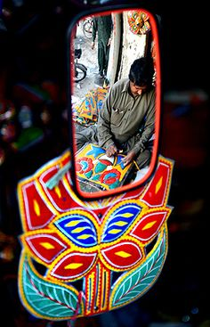 A Pakistani artisan reflected in a truck mirror works on making decorations for trucks and cars, in Rawalpindi.