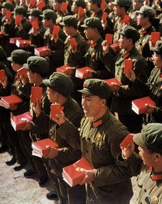 """Soldiers of the Chinese People's Liberation Army holding """"Quotations from Chairman Mao Tse-tung"""" in their right hand and the Selected works of Mao Tse-tung in their left hand during the Great Proletarian Cultural Revolution in the late"""