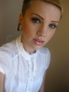 Short hair. Double nose ring. Medusa piercing and stretched earlobes.