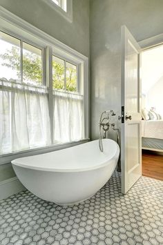 Amazing ensuite bathroom features walls clad in gray marble framing windows dressed in gray pinstripe cafe curtains situated over a modern egg shaped tub paired with a floor-mount vintage style tub filler atop large scale hex floor. Luxury Interior Design, Bathroom Interior Design, Bathroom Feature Wall, Feature Walls, Bathroom Colors, Bathroom Ideas, Bath Ideas, Bathroom Organization, Organization Ideas