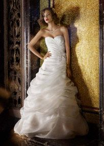 Simply divine, this dramatic organza gown is perfect for the ultra glamorous bride.  Strapless gown features angled draped pick-ups to create a stunning and slimming A-line silhouette.  Gorgeous sweetheart neckline highlights the shoulders while 3D floral embellishment at waist adds a modern touch.  Sweep train.  Fully lined. Dry clean only.  Available in limited stores and online in Soft White.    Shown wearing headpiece style C7545 and veil style VCT258Long.  To preserve your wedding dreams...